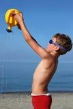 De jongen bevindt zich op strand en giet zand water geven-blik Royalty-vrije Stock Afbeelding