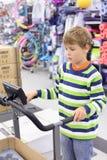 De jongen bevindt zich op trainertredmolen in sportenwinkel Stock Fotografie