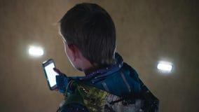 De jongen bevindt zich op de treden en draait een aantal op uw smartphone Mening van erachter stock video