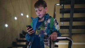 De jongen bevindt zich op de treden en kijkt zorgvuldig in de telefoon Sluit omhoog Emotionele staat stock video