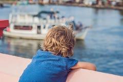 De jongen bewondert het overzees en de kleurrijke die boten in Phu Quoc Vietnam wordt vastgelegd De boten zoals deze zijn iconisc Royalty-vrije Stock Foto
