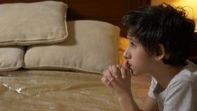 De jongen bidt vóór bed, 4k stock videobeelden