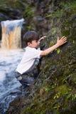 De jongen bij de waterval Stock Afbeelding