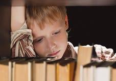 De jongen bij een boekenkast krijgt het boek. stock afbeeldingen