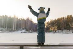 De jongen bij het bevroren meer geniet van zonlicht royalty-vrije stock foto's