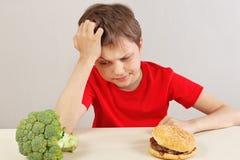 De jongen bij de lijst kiest tussen hamburger en verse broccoli op witte achtergrond stock afbeeldingen