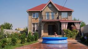 De jongen in de binnenplaats van een buitenhuis in de zomer ontspant het spelen met waterslang stock video