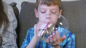 De jongen blaast grote bellen van op slimes Spel met slijm stock video