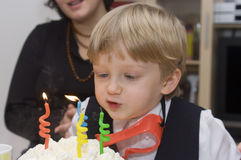 De jongen blaast in kaarsen op verjaardagscake Royalty-vrije Stock Foto