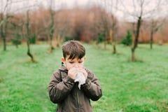 De jongen blaast zijn neus in de sjaal De allergie is toe te schrijven aan het bloeien stock afbeeldingen