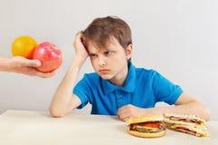 De jongen in blauw bij de lijst kiest tussen fastfood en vruchten royalty-vrije stock fotografie