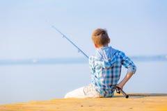 De jongen in blauw overhemd zit op een pastei Stock Foto