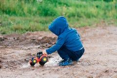 De jongen in blauwe kostuumspelen met een stuk speelgoed auto in het vuil royalty-vrije stock fotografie