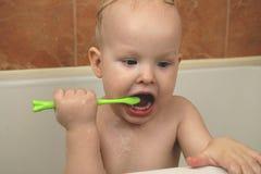 De jongen borstelt zijn tanden in de badkamers teething Het concept mondelinge hygiëne stock afbeeldingen