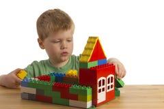 De jongen bouwt een huis Stock Foto's