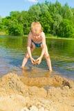 De jongen bouwt een zand Stock Afbeelding