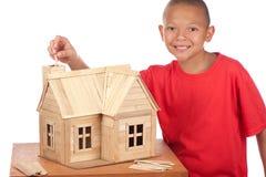 De jongen bouwt ijslollyhuis Stock Afbeeldingen