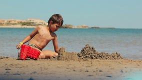 De jongen bouwt zandkastelen stock video