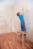 De jongen breekt behang van muur Stock Afbeeldingen