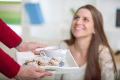 De jongen brengt zijn meisje op een dienbladkoffie en koekjes Stock Fotografie