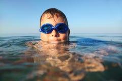 De jongen in bril voor het zwemmen zwemt in overzees stock fotografie