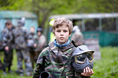 De jongen in camouflage houdt paintball kanonvat tegen royalty-vrije stock afbeeldingen