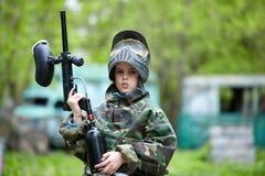 De jongen in camouflage houdt tegen een vat van het paintballkanon stock foto's
