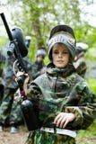 De jongen in camouflagekostuum houdt een paintballkanon royalty-vrije stock foto's