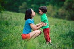 De jongen communiceert met zijn moeder in aard Royalty-vrije Stock Afbeelding