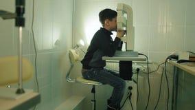 De jongen controleert oogvisie in oftalmologiekliniek - brede hoek stock footage