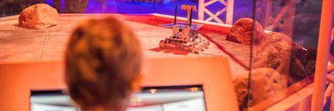 De jongen controleert de stuk speelgoed zwerver op Mars Vlucht aan het conceptenbanner van Mars, LANG FORMAAT stock fotografie