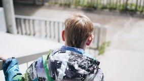De jongen daalt snel de treden in de passage onder de brug De camera volgt hem Langzame playback stock footage