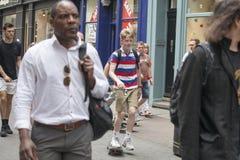 De jongen in de gestreepte T-shirt die door de menigte schaatsen Stock Afbeeldingen
