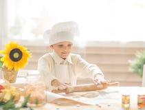 de jongen in de vorm van een kok ontwikkelt het deeg Royalty-vrije Stock Fotografie
