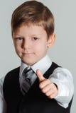 De jongen die duimen geven ondertekent omhoog Stock Foto's