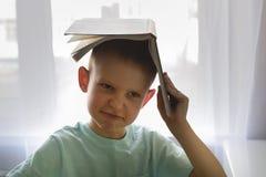De jongen die een boek over uw hoofd houden, wil niet lezen stock afbeelding