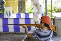 De jongen die een geweerstuk speelgoed houden die van hout wordt gemaakt stock foto's