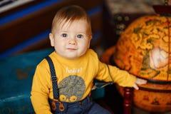 De jongen die met mollige wangen naast een bol glimlachen stock foto
