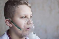 De jongen die met wit haar in het inhaleertoestel ademen royalty-vrije stock foto's