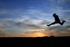 De jongen die op de rotsen springen Stock Fotografie