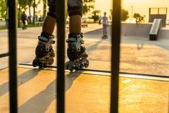 De jongen die in openbaar park met beschermingsmateriaal rollerblading op de zonsondergangachtergrond stock foto's