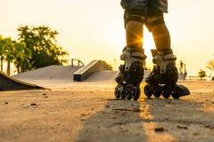 De jongen die in openbaar park met beschermingsmateriaal rollerblading op de zonsondergangachtergrond stock foto