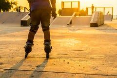 De jongen die in openbaar park met beschermingsmateriaal rollerblading op de zonsondergangachtergrond royalty-vrije stock foto