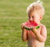 De jongen die van de één éénjarigebaby watermeloen in de tuin eten Stock Afbeeldingen