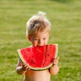 De jongen die van de één éénjarigebaby watermeloen in de tuin eten Stock Fotografie