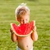 De jongen die van de één éénjarigebaby watermeloen in de tuin eten Stock Foto's