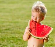 De jongen die van de één éénjarigebaby watermeloen in de tuin eten Royalty-vrije Stock Foto