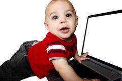 De Jongen die van de baby aan laptop werkt. Stock Fotografie