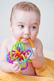 De Jongen die van de baby aan Multicolored Stuk speelgoed op Gele Handdoek knaagt Royalty-vrije Stock Afbeelding