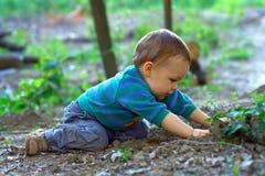 De jongen die van de baby de grond in de lentebos graaft Stock Afbeeldingen